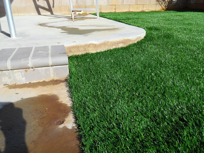Backyard synthetic lawn with concrete steps