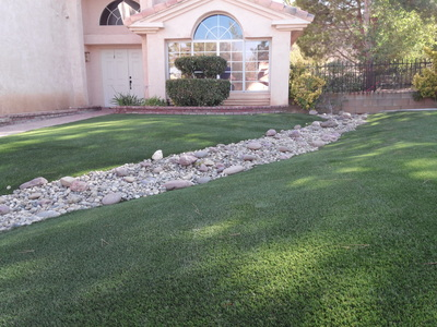 Artificial grass yard with landscape rock